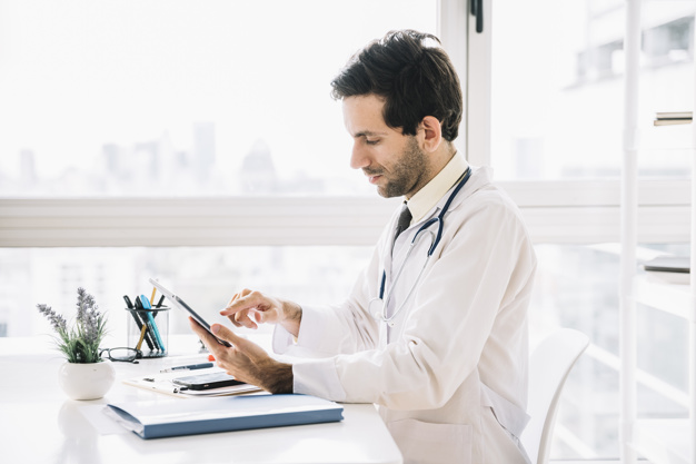 side-view-male-doctor-using-digital-tablet-clinic_23-2147941770